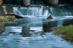 Part of the concrete structure of the river dam. Water blurred b stock photo