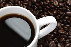 Part of cup of coffee and coffee beans Royalty Free Stock Photography