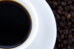Black Coffee and Beans. Part of a cup filled with black coffee with matching plate on background of coffee beans. Shot from high angle Royalty Free Stock Images