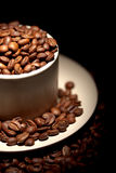 Part of cup full of golden coffee beans Royalty Free Stock Photo