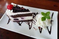 Part de gâteau de forêt noire de chocolat avec une cerise Images stock