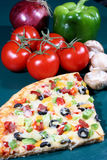 Part de pizza et légumes frais Images stock