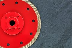 A part of a diamond cutting wheel is red with a threaded nut on a background of gray granite stock photo