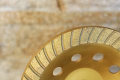 Part of the diamond grinding wheel on background an orange-golden sandstone wall royalty free stock images