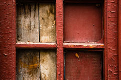 Part of door. With four small windows, what clogged with plaque. The old red paint on the door Stock Photography