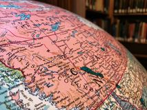 Part of the Earth globe with a political map on the background of books. Canada royalty free stock images