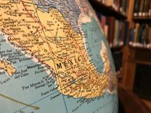 Part of the Earth globe with a political map on the background of books. Mexico stock photos