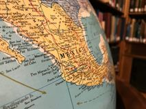 Part of the Earth globe with a political map on the background of books. Mexico royalty free stock photos