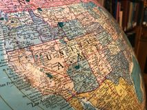 Part of the Earth globe with a political map on the background of books. USA royalty free stock photo