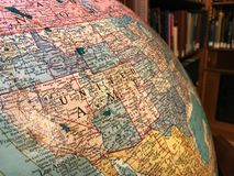 Part of the Earth globe with a political map on the background of books. USA stock images