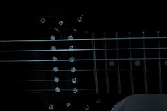 Part of the electric guitar on black background. A place for writing of the text. Royalty Free Stock Photography