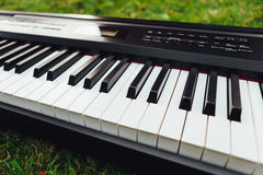 Part of electric piano keyboard, green grass background Stock Images