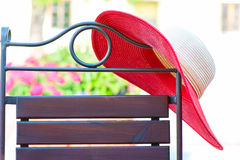 Part of elegant metal curved chair and red summer hat on patio. Royalty Free Stock Photography