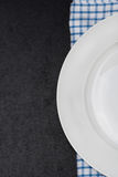 Part of the empty plate on napkin and black background for text Stock Photo
