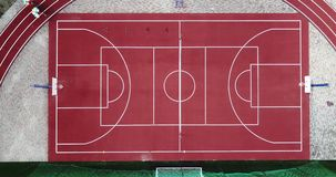 Part of empty sport playground stadium from birds eye view. Red sport ground for playing big tennis and basketball and. With a green Football soccer field and stock footage