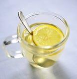 Part et cuillère de citron dans la tasse en verre d'eau chaude