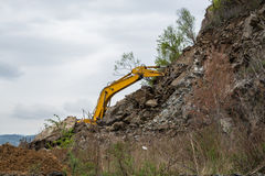 Part of excavator behind the slope. Royalty Free Stock Photos