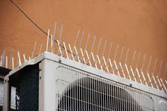 Part of the facade of the building with plastic spikes against pigeons. the design does not allow birds to sit down and shit. Vert. Ical plastic spikes in two Royalty Free Stock Photo