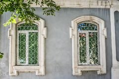 Part of the facade of a gray old stone house with two windows in white platbands. Part of the facade of a gray old stone house with two wndows in white royalty free stock image