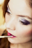 Part of face. Woman applying pink lipstick with brush Royalty Free Stock Image