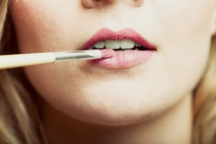 Part of face. Woman applying pink lipstick with brush Royalty Free Stock Photos