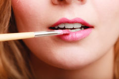 Part of face. Woman applying pink lipstick with brush Royalty Free Stock Images
