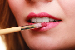 Part of face. Woman applying pink lipstick with brush Stock Photos
