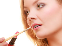 Part of face. Woman applying pink lipstick with brush Stock Image