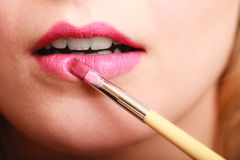 Part of face. Woman applying pink lipstick with brush Royalty Free Stock Photo