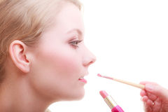 Part of face. Woman applying red lipstick with brush Stock Photo