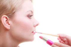 Part of face. Woman applying red lipstick with brush Stock Photos