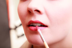 Part of face. Woman applying red lipstick with brush Royalty Free Stock Image