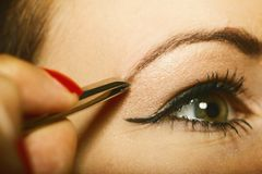 Part of face woman plucking eyebrows. Depilating with tweezers stock image
