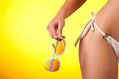 Part of female body with white bikini. And sunglasses on yellow background Royalty Free Stock Photo