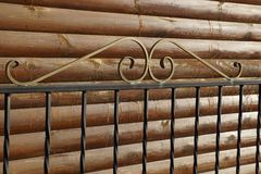 Part of the fence of black metal rods against a wooden brown wall. Part of the fence made of black metal rods with a wrought pattern against a wooden brown wall stock photos