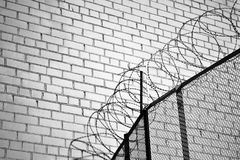 Part of the fence made of metal mesh and barbed wire on the background of brick wall. Black and white stock images