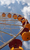 Part of Ferris wheel. Orange and red cars on a big Ferris wheel with a blue sky at the back Royalty Free Stock Photo
