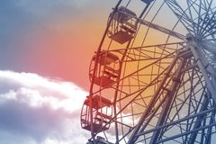 Part of a Ferris wheel against a blue sky with a light stock image