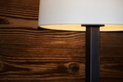 Part of a floor lamp against wooden wall royalty free stock photography