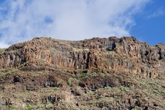 Mountain under a blue sky with a white cloud. Part of the the Fortaleza of La Gomera with a white cloud Stock Photography