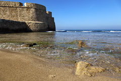 Acco's City Wall & Seashore. Part of the fortified wall surrounding the ancient city of Acco (Israel), bordering with the shore of the Mediterranean sea, on a Royalty Free Stock Images