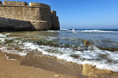 Acco's City Wall & Seashore. Part of the fortified wall surrounding the ancient city of Acco (Israel), bordering with the shore of the Mediterranean sea, on a Stock Image