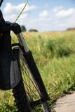 Part of the front wheel with resors against the background of the spring green rye field and red poppies stock photos