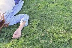 Part of girl lay on grass and rise hand dress in jeans. Stock Photos
