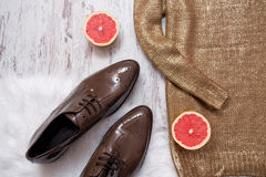 Part of a golden sweater, brown patent leather shoes and grapefruit, wooden background. Fashionable concept. Royalty Free Stock Photography