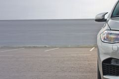 Part of the gray car on the background of the wall stock photo