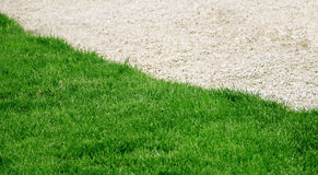 Part of a green lawn with small pebbles Stock Photo