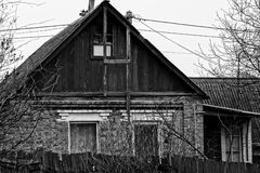 Part of grey rural house after a wooden fence Royalty Free Stock Photo