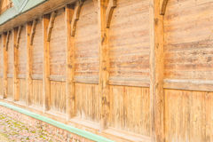 Part of the house, namely a wall without windows, built of wooden boards with the use of bearing vertical supports Stock Photography