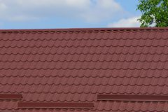 Part of the house with a roof under the brown tile against the sky royalty free stock photo